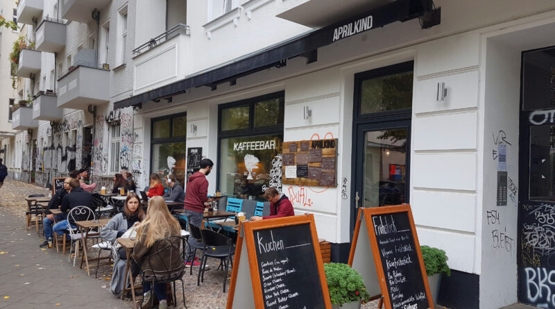 Side view of the coffee bar Aprilkind in Berlin with guests sitting in front of it.