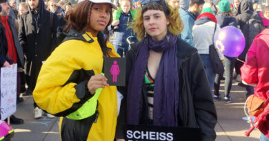 """2 people at the International Women's Day in Berlin 2019 with the CO-WC sign and a poster with the inscription """"Scheiß Patriarchat Elendiges."""""""