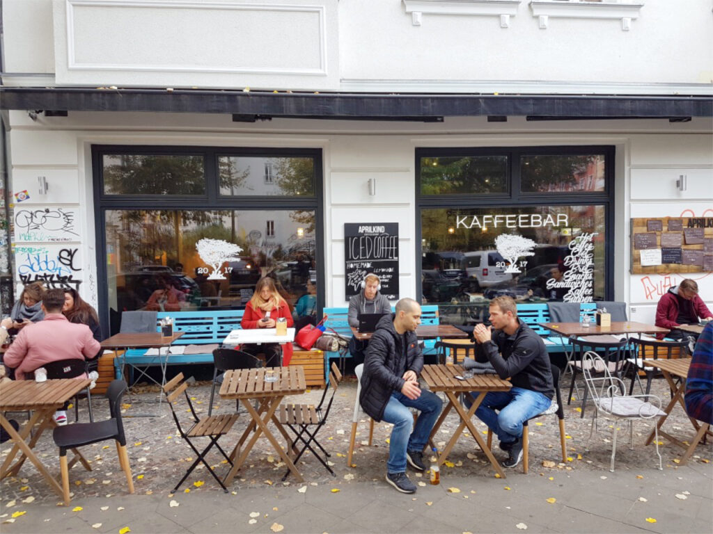 Front view of the coffee bar Aprilkind in Berlin with guests sitting in front of it.