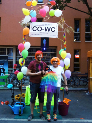 Two people in wigs at the information booth with the CO-WC sign and mascot.