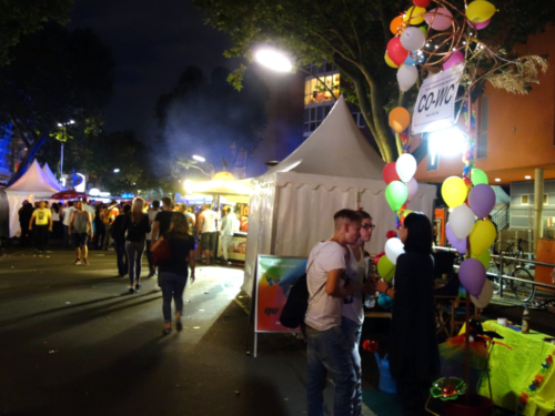 CO-WC info booth at the Lesbian and Gay City Festival by night.