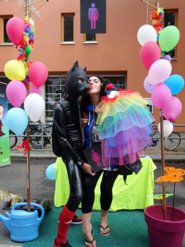 Two people from the Lesbian and Gay City Festival at the CO-WC information booth, the one in the dog costume gets a kiss.