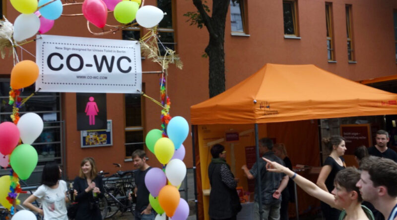 Person points with her finger at the CO-WC info booth at the Lesbian and Gay City Festival in Berlin.