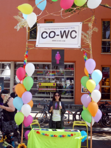 Shinhee Chae at the CO-WC info booth with the sign in her hands.