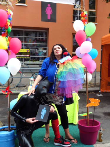 Two visitors to the Lesbian and Gay City Festival at the CO-WC information booth, one in a dog costume.