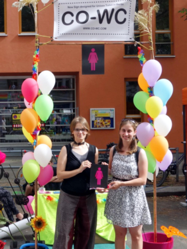 Visitors of the Lesbian and Gay City Festival with the CO-WC sign.