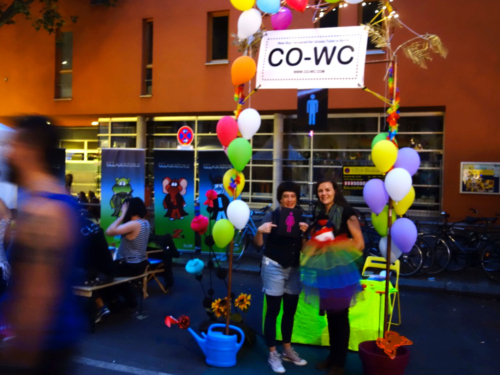 CO-WC info booth at night with two visitors of the Lesbian and Gay City Festival.