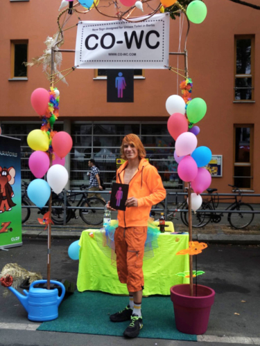 Visitors to the Lesbian and Gay City Festival at the CO-WC information booth, dressed in orange and holding the umbrella sign.