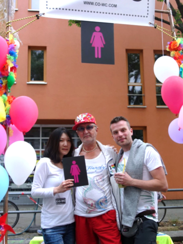 Shinhee Chae with the CO-WC sign and two visitors to the Lesbian and Gay City Festival.