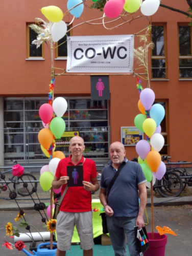 Two people at the Lesbian and Gay City Festival holding the CO-WC sign.