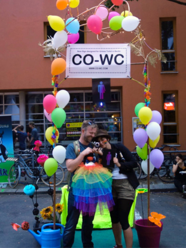 Two people at the CO-WC information booth, holding the sign, the mascot, and a camera.