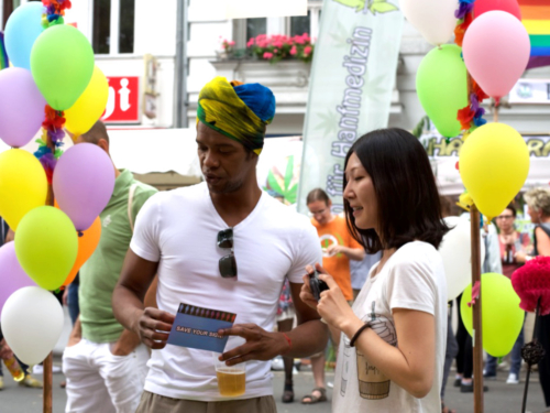 Shinhee Chae with a festival-goer at the CO-WC information booth surrounded by balloons.