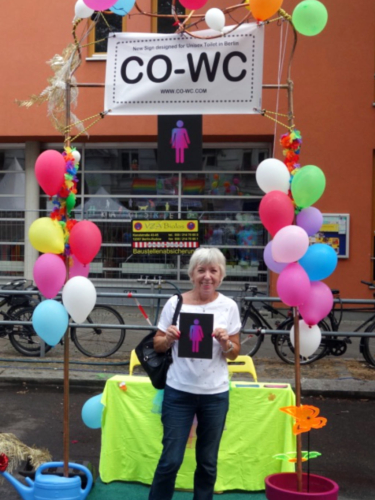 Elderly person stands in the information booth with the CO-WC sign.