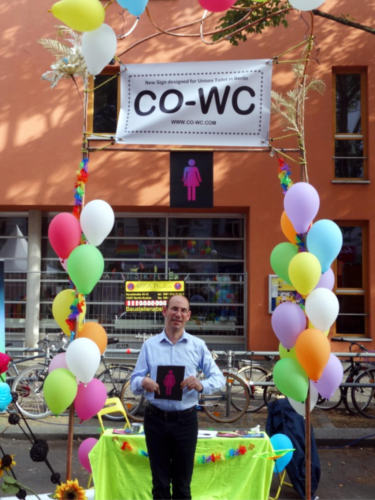 One Person in front oft the info booth holding the CO-WC sign in both hands.