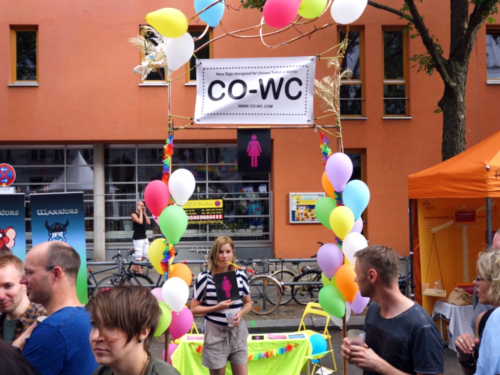 Person in front of CO-WC info booth, with the sign in hand and observed by visitors of the Lesbian and Gay City Festival.