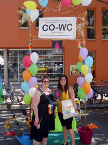 Two people in front of the CO WC info booth, with the sign and a rainbow flag.