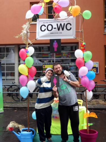 Two people are standing in front of the CO-WC info booth and one person is giving the thumbs up.