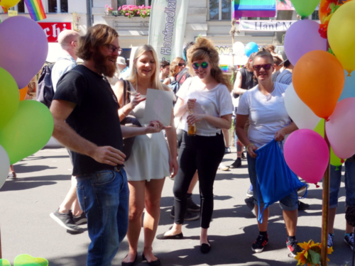 Paul Jonczyk talks to visitors of the Lesbian and Gay City Festival in front of his information booth and shows them a CO-WC sign.