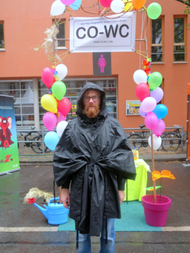 Paul Jonczyk stands in a raincoat in front of the CO-WC information booth.