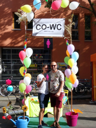 Two people perform with the CO-WC sign at the information booth.