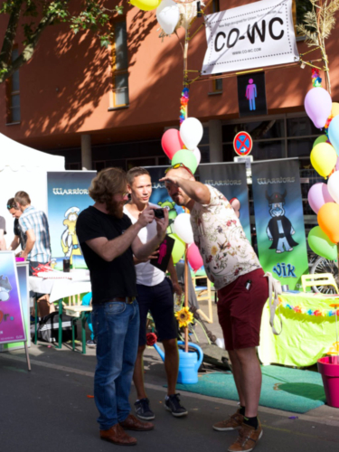 CO-WC founder Paul Jonczyk shows a photo shot to some visitors at the Lesbian and Gay City Festival.